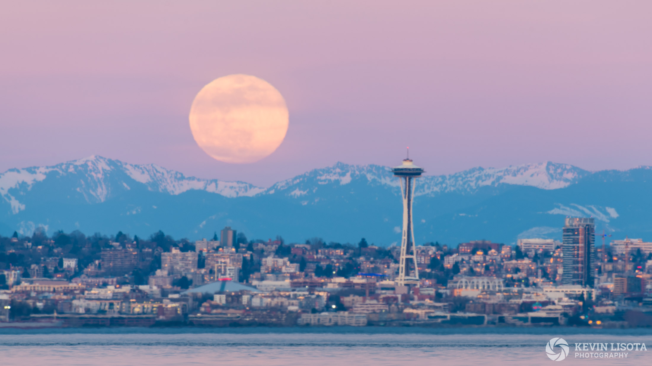 Moonrise over Seattle and the Cascade Mounts showing strong heat distortion from the cold water of Puget Sound.b