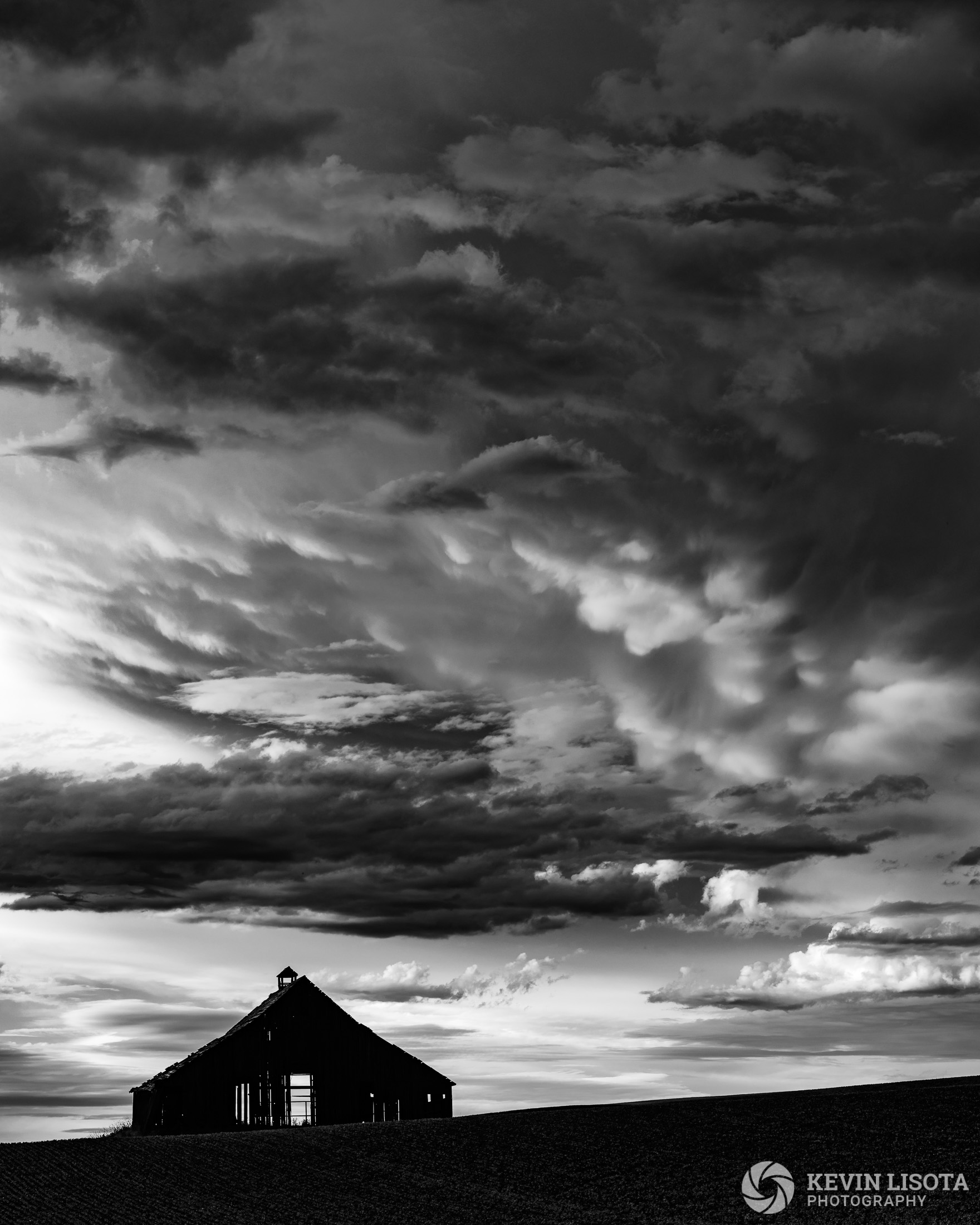 Thunderstorm clouds over old barn at Ladow Butte
