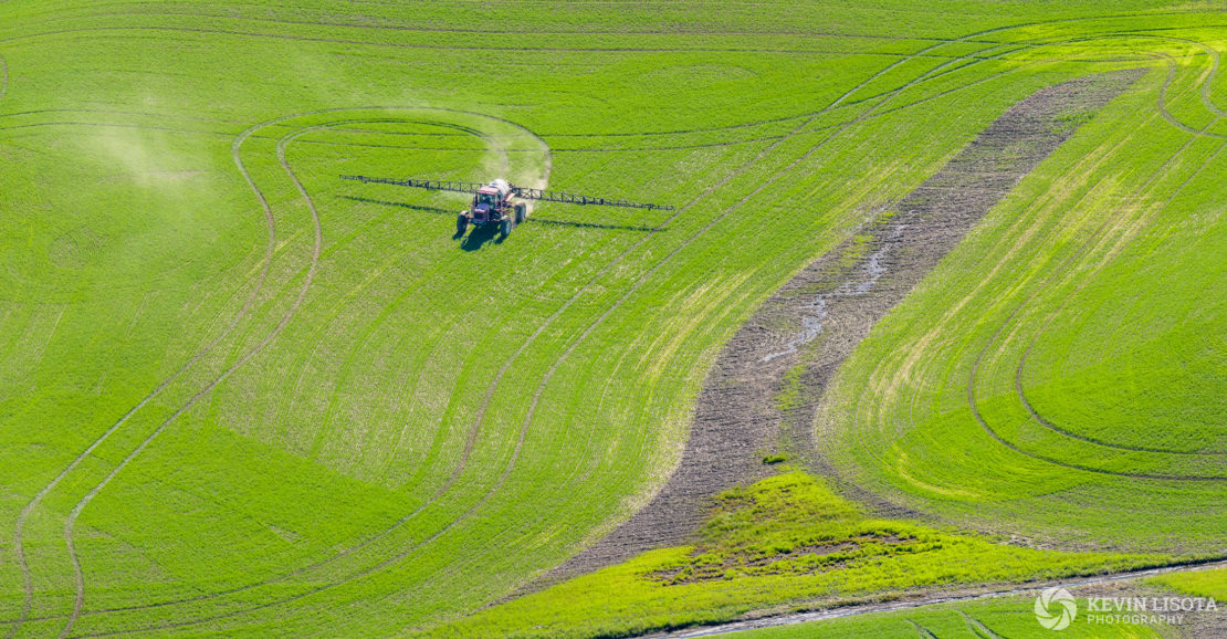 Tractor spraying crops in the Palouse