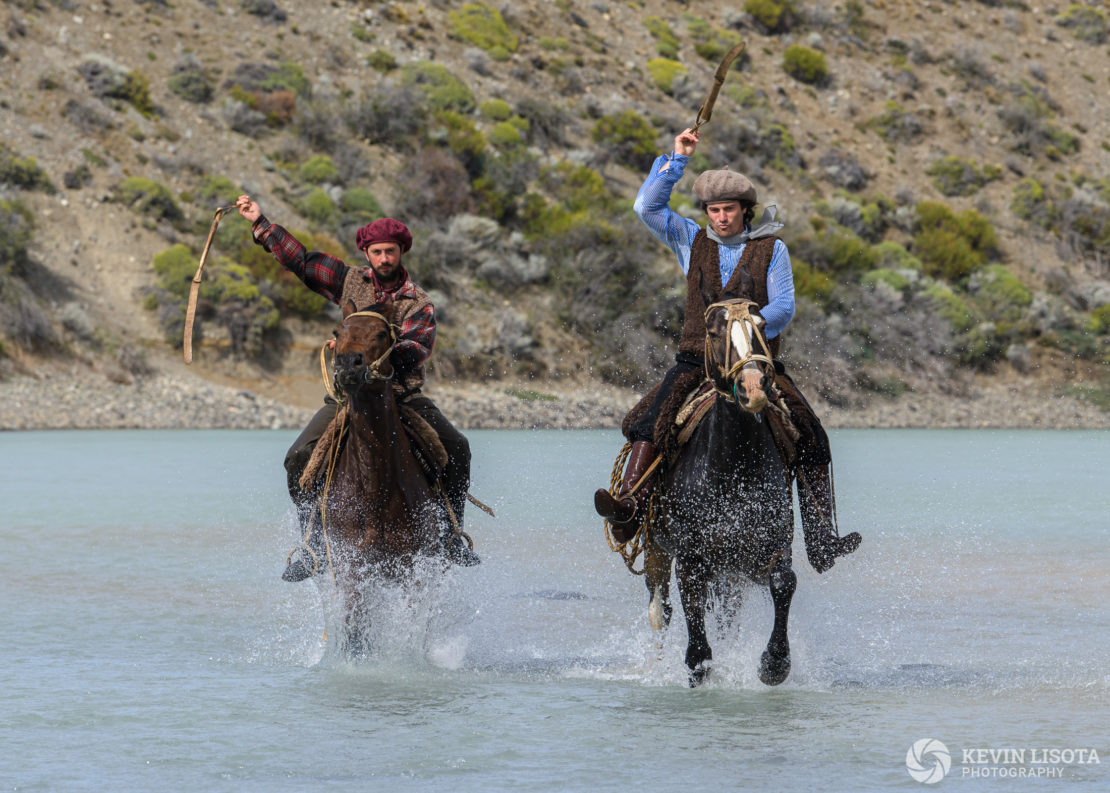 Gauchos on horseback in the La Leona River of Patagonia