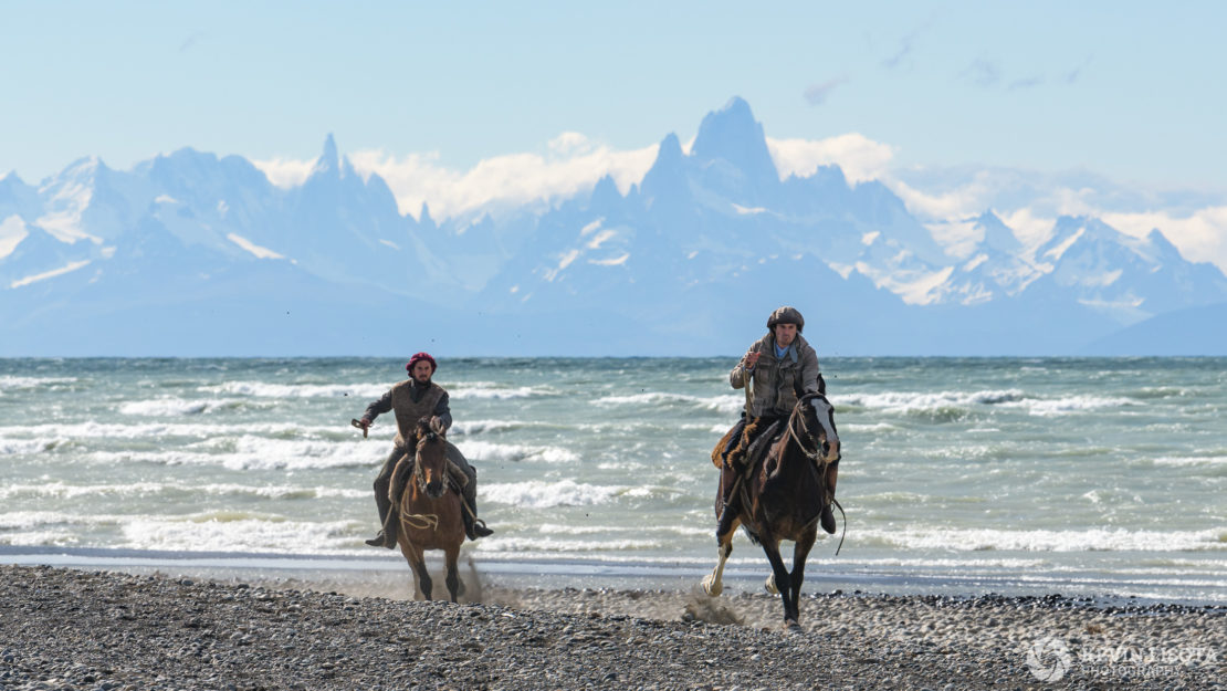 Gauchos gallop on the shore of Lake Viedma