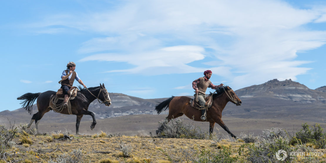 Gauchos gallop across the Patagonia plains on horseback