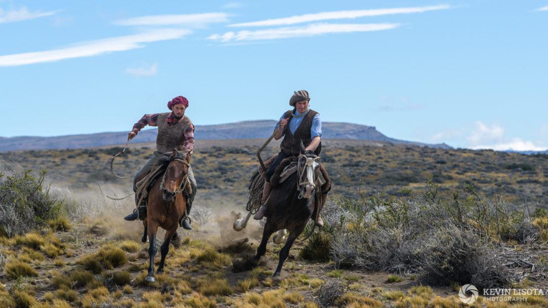 Gauchos gallop on horseback in Patagonia